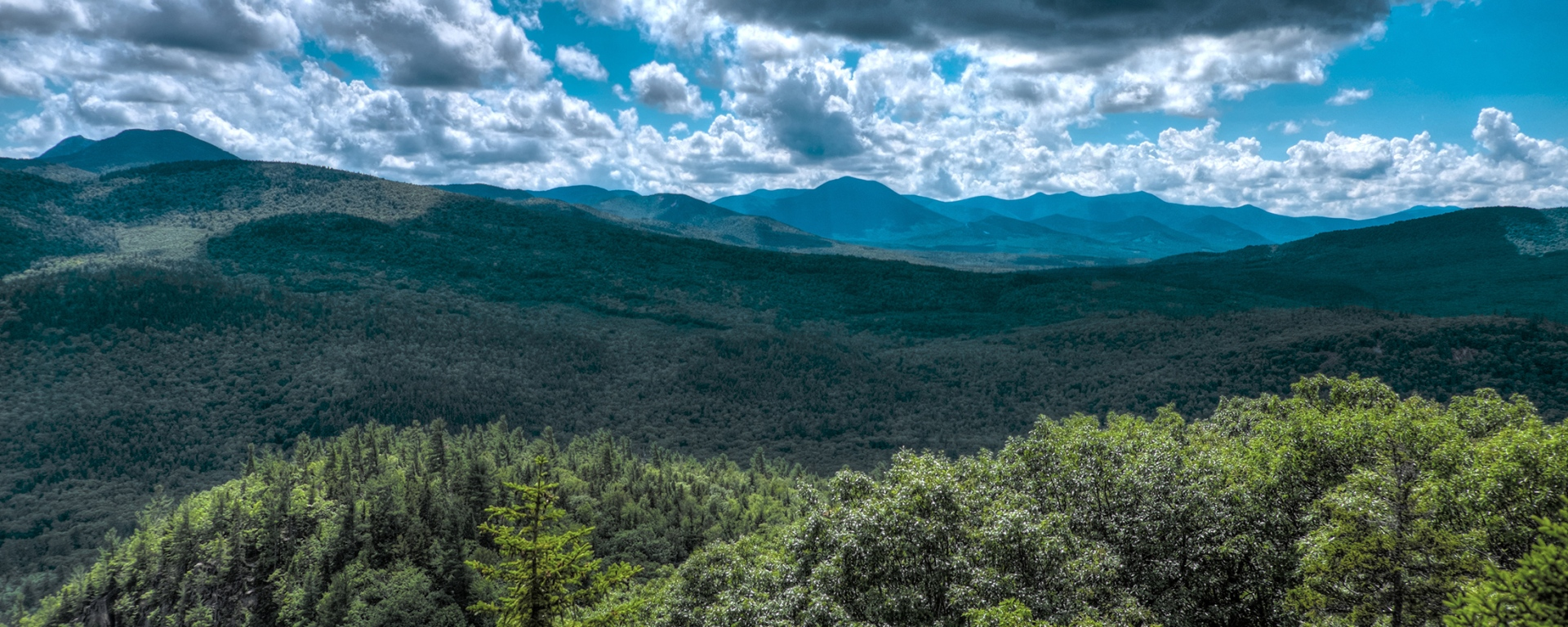 A looming rain cloud sits above the boulder loop trail in the White Mountains of New Hampshire