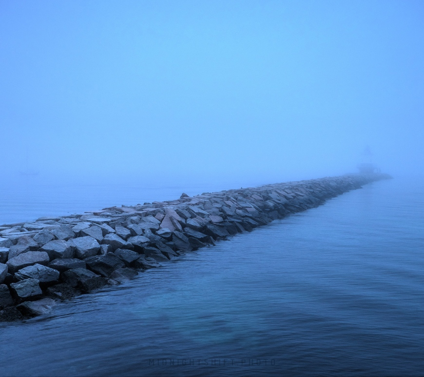 The spring point ledge lighthouse in South Portland, Maine sits in the dense fog.